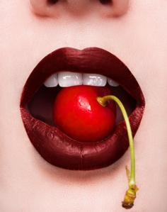 Photo of a beautiful woman's mouth with a cherry between her teeth