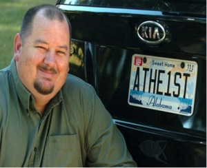 "Photo of a man sitting next to his car, which has a license plate that reads, ""ATHE1ST."""