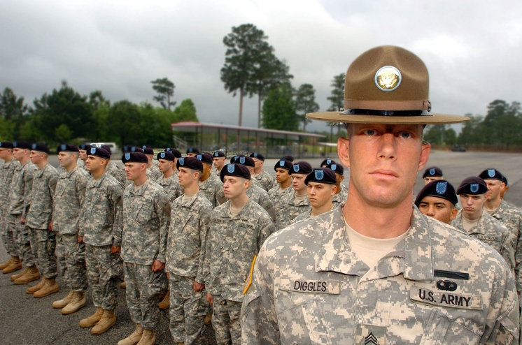 Photo of an Army drill sergeant standing in front of three long rows of recruits standing in formation, looking stern