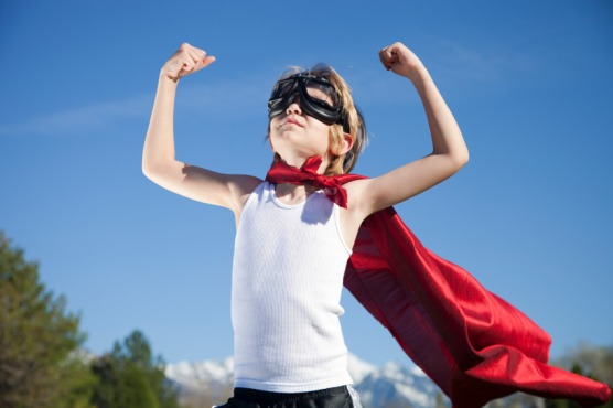 Picture of a boy wearing a Super Man cape, holding his arms up triumphantly and looking confidently at the sky