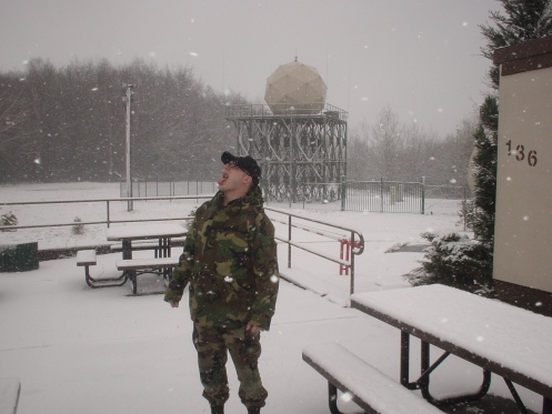Picture of me wearing a military cold-weather uniform in the snow behind my office in Sembach Germany. In the distance are pine trees and a weather radar