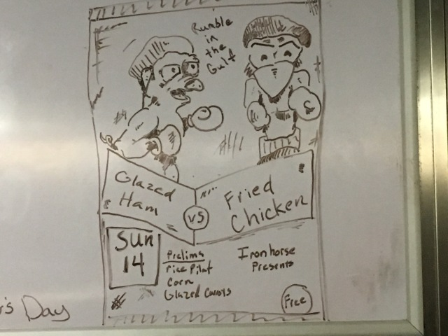 """Picture of a boxing match poster with two chickens dressed like boxers on it. Above them it says, """"Iron Horse Presents: Rumble in the Gulf."""" Below them it says, """"Sunday 14: Glazed Ham vs Fried Chicken"""