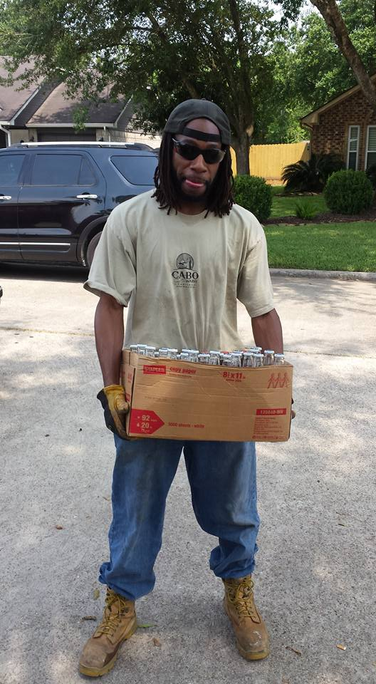 Photo of a random African American dressed in dirty work cloths, holding a cardboard box containing 30 Corona beer bottles