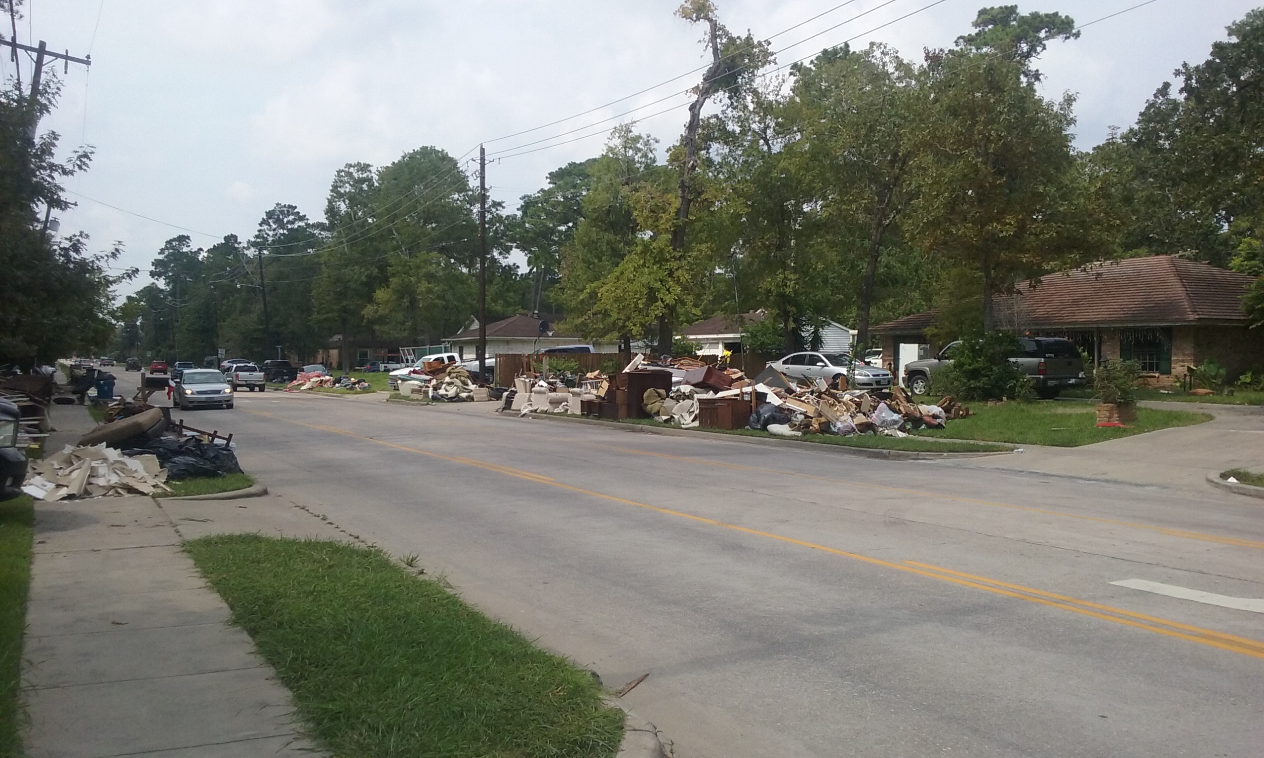 Photo of a suburban street with small houses. All the yards are covered in furniture and trash from gutting houses after Hurricane Harvey