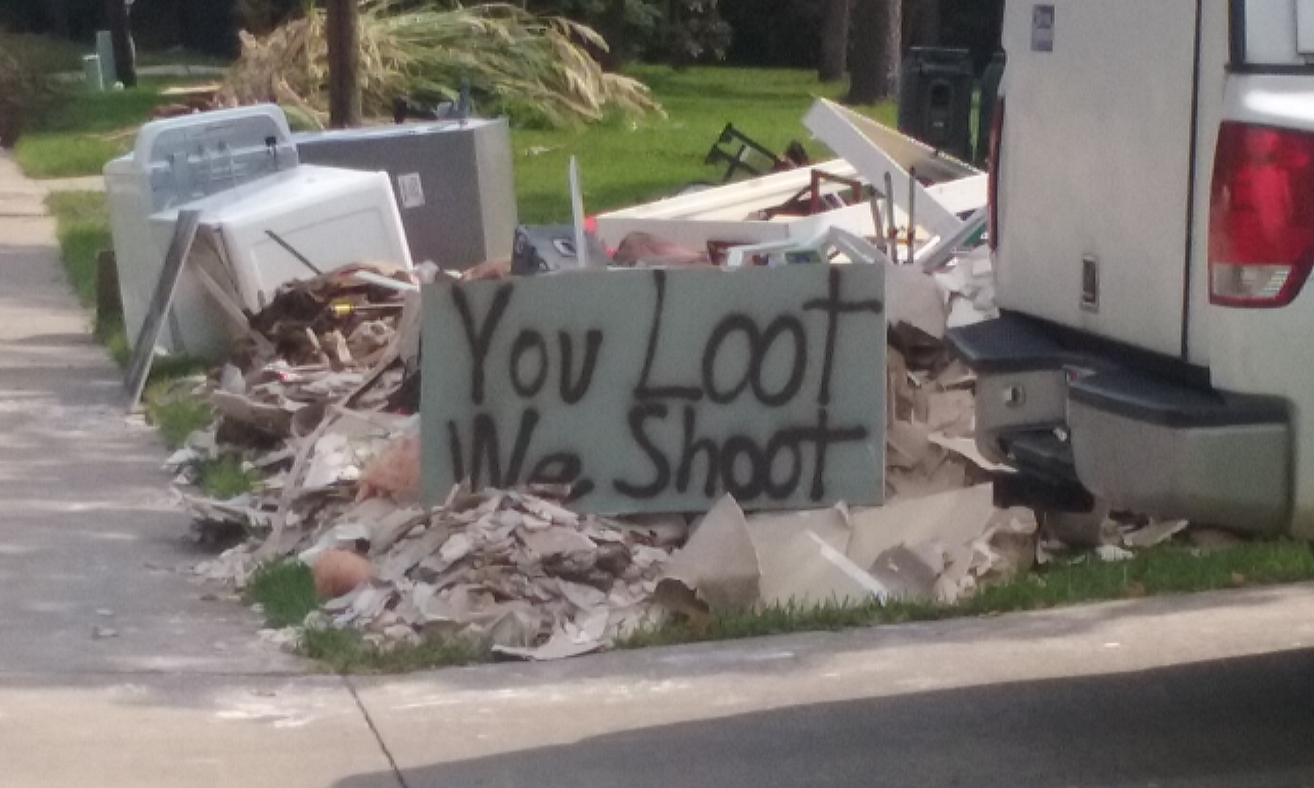 "Photo of a spray-painted sign sitting on a pile of debris by the side of the street in Dickinson, Texas after Hurricane Harvey. The sign says, ""YOU LOOT. WE SHOOT."""